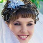 Фото прически с короткой челкой и синим цветком. Вид спереди.