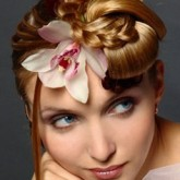 Фото высокой прически с плетением и цветком. Вид спереди.