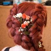 Две толстые косы наружу переходят в одну, прическа украшена живыми цветами
