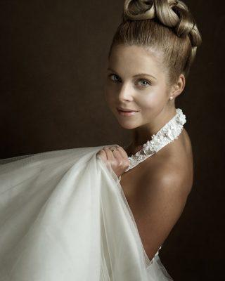 Высокая свадебная прическа с акцентом на аккуратно сплетенные локоны.