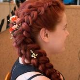 Вид сбоку прически с косами на густые рыжие волосы