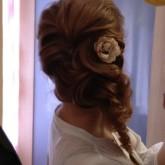 Фото пышной косы с цветком в тон. Вид сзади.