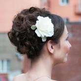 Фото высокой прически с крупным белым цветком. Вид сбоку.
