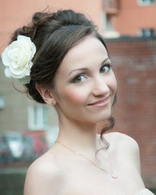 Фото высокой прически с крупным белым цветком. Вид спереди.