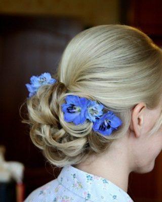 Фото прически с синими цветками на светлых волосах. Вид сзади.