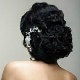 Фото прически из темных волос со светлым украшением. Вид сзади.