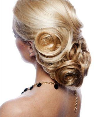 Ассиметричная прическа на густые волосы, которые уложены завитками на низком пучке