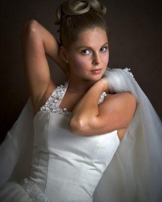Свадебная прическа с волосами, собранными на макушке.