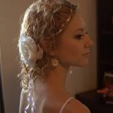 Фото свадебной прически из мелких завитков с розой, вид сбоку.