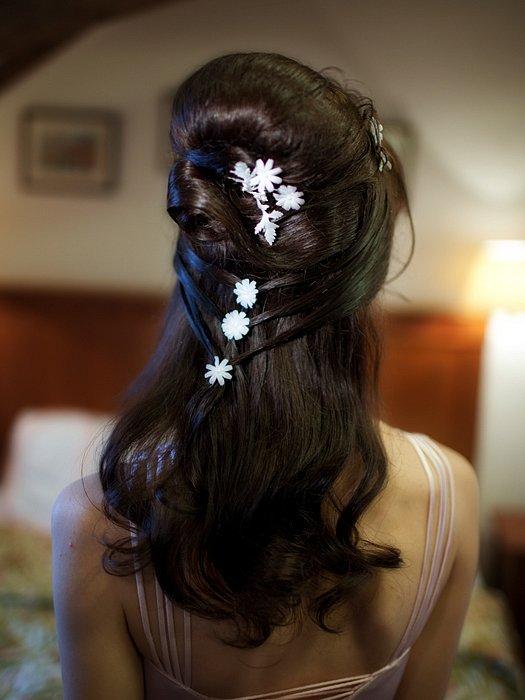 Фото тордественной прически на темных волосах с мелкими цветками. Вид сзади.