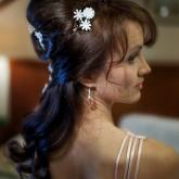 Фото тордественной прически на темных волосах с мелкими цветками. Вид сбоку.