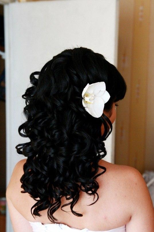 Фото прически на темных волосах со светлым цветком сбоку. Вид сзади.