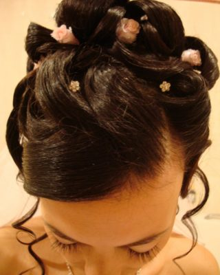 Фото торжественной прически из темных волос с выпущенными прядями по бокам.