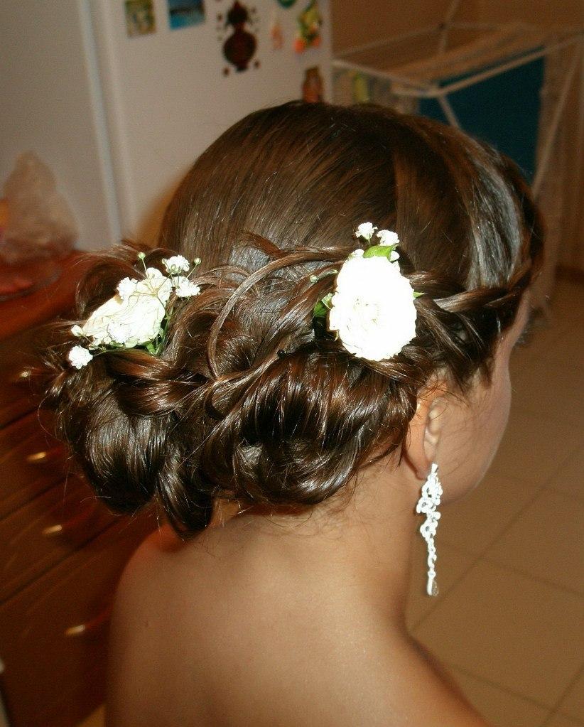Фото высокой прически с белыми цветами на темных волосах.