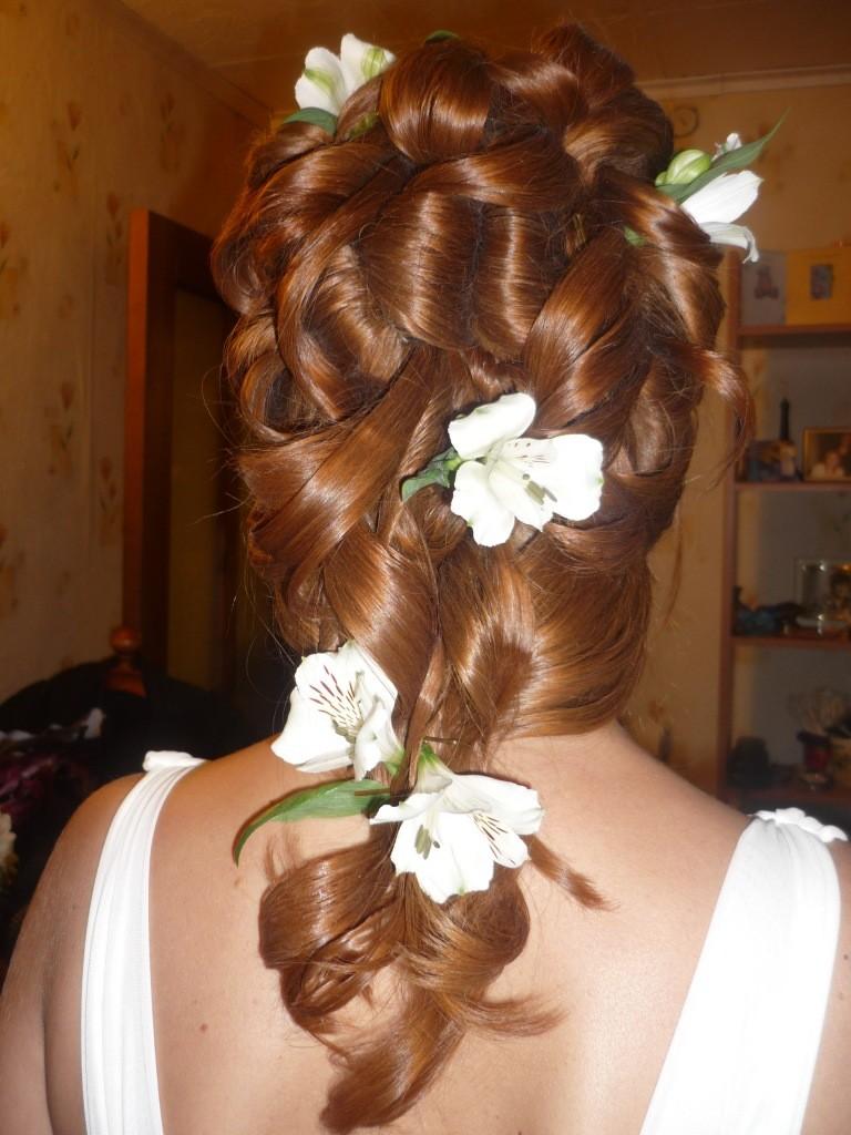Фото свадебной прически из накрученных рыжих волос с цветами.