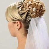 Восхитительная высокая прическа на свадьбу изящно украшена нежными цветами и фатой