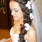 Красивая коса набок дополнена цветами и фатой