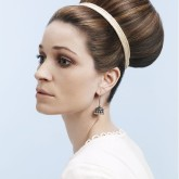 Волосы, собранные в пучок, украшены атласной лентой