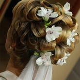 Изящные локоны и живые цветы идеальны для свадбеной прически