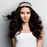 Пышные распущенные волосы красиво сочетаются с блестящим ободком