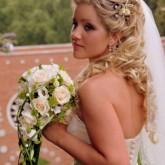 Свадебная прическа с изящными цветами, кудрями и фатой