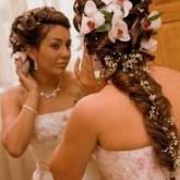 Красивая коса торжественно сочетается с крупными цветами