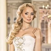 Прекрасная свадебная прическа с локонами, собранными сбоку