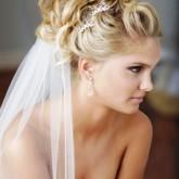 Высокая свадебная прическа с локонами и белоснежной фатой